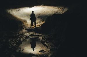 man-exploring-dark-cave-underground-tunnel-UQ3V8GJ-min